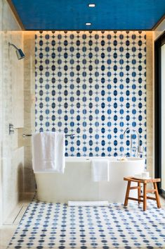 A blue lacquered ceiling, blue tiles, and a modern soaking tub offer a relaxing escape. #bathroom #bathtub #tile #bathroomtile