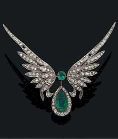 A Belle Epoque gold, emerald and diamond brooch, early 20th century. Designed as a pear-shaped emerald within a diamond-set frame, surmounted by a round emerald and flanked by a pair of wings set wtih rose-cut diamonds, mounted in 18k gold.