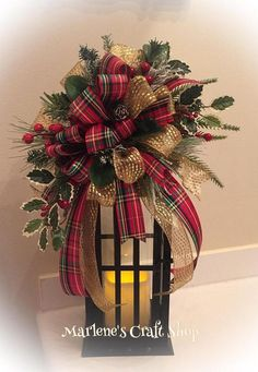 This Stunning Christmas Lantern Swag is full of details! The Lantern Swag is pictured above on a 14 inch Lantern. The Swag features two Christmas ribbons. One in sparkly gold and the second ribbon in traditional plaid Christmas Colors of Red,Gold, and Green. The swag also features