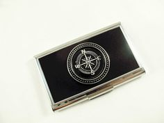 This Nautically inspired business card holder features a silver compass in a silver frame on the front. The finely finished gloss black and silver