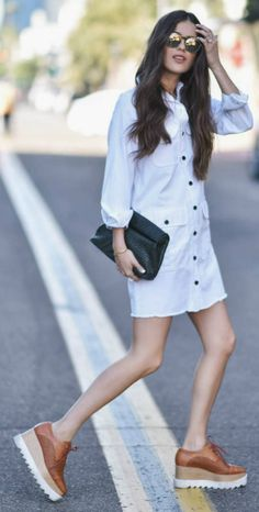 A white shirt dress is the perfect choice for a fun and simple spring look. Paola Alberdi looks cute and summery in this mini dress, worn with a pair of edgy platform brogues and classic retro shades. Dress: Fifteen Twenty, Shoes: Stella McCartney, Bag: Marie Turnor.