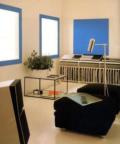 "80sdeco: "" Bang & Olufsen beocenter, record and tape console, black metal and glass table, double ottoman, chrome floor lamp, Pantone blue accents """
