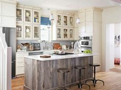 Classic country: barn-wood island, apron-front sink, and beadboard cabinets. #kitchens