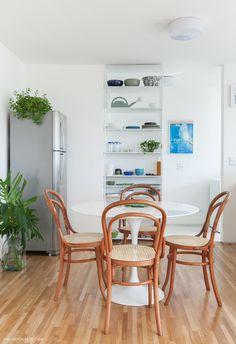"""Armário """"dupla face"""" metálico, cadeiras thonet e mesa saarinen compõem essa cozinha."""