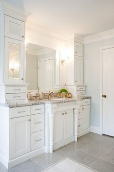 Chic bathroom features ceiling height cabinets with mirrored doors flanking framed mirror over white vanity with white carrera marble top sink accented with carved legs over gray tile floor.