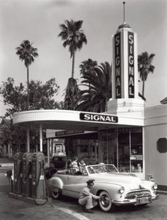 Getting some air in the tyres at a gas station, circa 1950.