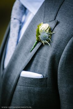 Bruidscorsage met witte roos en paarse distel. Wedding corsage with white rose and purple thistle.