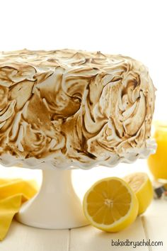 Homeamde three tiered lemon meringue cake featuring layers of moist lemon cake, fresh lemon curd and meringue frosting! A perfect dessert for Spring!