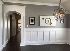 Upgraded trim with columns, arches, wainscoting, baseboards and crown molding in Modern home. Gray walls with crisp white trim. Minimalist black picture frames and globe chandelier. See how it came together over at SovereignCarpentry.com