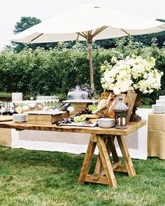 Great floral setting on the corner of this rustic table - love the height of the cheese tray and glasses.