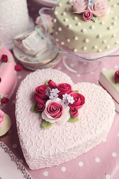 Heart shaped pink cake with pink and red sugar roses