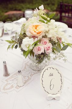 The round tables will have lanterns paired with two pieces of vintage glassware or mason jars filled with ivory garden roses, Queen Anne's lace, light blue delphinium, lavender scabiosa, ivory stock flowers, and white waxflowers surrounded by mercury glass votives.