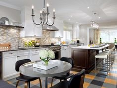 Known for her super luxe, traditional spaces, design diva Candice Olson focused on function as well as form when designing this long galley-style kitchen for a busy family of four. She chose white wall cabinets to keep the space bright but decided on a dark stain for the island to break things up. Gray, gold and black linoleum floor tiles add a playful touch and echo the colors found in the glass tile backsplash.