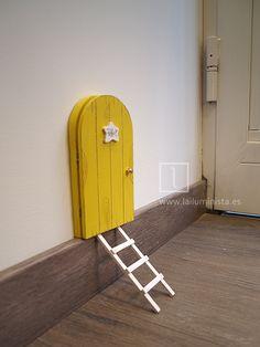 Puerta para el ratoncito Pérez que se abre en color amarillo. La placa con el nombre de Pérez es blanca tiene forma de estrella. Está hecha a mano y en su interior se puede ver la ilustración de la cueva a través de la cual viaja el ratoncito Pérez.