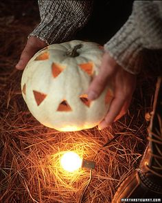 Line your walkway or front porch with Christmas lights, plugged into an outside socket or heavy-duty extension cord, and position a pumpkin over each lightbulb.