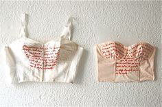 1950 - 2010 (2010)    On the left, a vintage bra from the 1950s. On the right, 2010 H corset, red thread.    Embroidered on the vintage garment, a text from the Sección Femenina (Franco's female group) pieces of advice to young women. On the modern corset, a paragraph from a spring 2010 issue of the Spanish edition of Elle magazine.