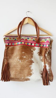 Awesome cowhide bag with a pop of color and leather fringe tassels.: