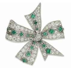 AN EMERALD AND DIAMOND BOW BROOCH. Of multiple loop design, millegrain-set throughout with square-cut emeralds interspersed by diamond single stone collets to an openwork ground, between diamond line borders, with baguette-cut diamond knot centre, circa 1930, 3.5cm wide
