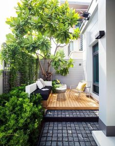 A contemporary terrace with a built-in bench in black and white, a deck, a comfy chair and a coffee table.