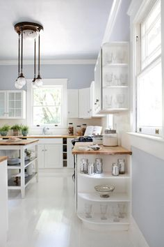 Anytime you're looking to make a kitchen seem larger and keep it from looking dated, consider using white and muted gray tones. The two colors paired together will help capitalize on all natural light and also keep the space feeling clean.