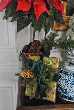 The Enchanted Home Christmas vignette with a festive gift wrapped in gold paper with dark green velvet ribbon!!! Bebe'!!! Love the pinecone topper!!!