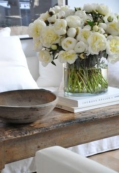 Rough wood offset with white coffee table books, glass, water and lush flowers. textures everywhere
