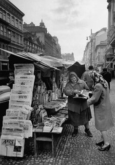 A news vendor helping a woman find which magazine she would like to buy at the stand. Photograph by Walter Sanders. Prague, Czechoslovakia, December 1947.