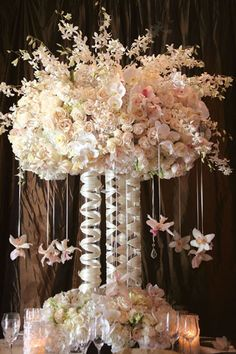 Towering centerpieces, perfect for a high-ceilinged space, add drama and elegance to tables. This centerpiece features ivory roses, white hydrangeas, and white and pale-pink orchids, with cymbidium orchids on satin ribbons.  http://roxyheartvintage.com