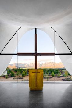 A bright white canopy undulates above the glazed walls of this chapel outside Cape Town, framing views right through it to scenic mountains, vineyards and pomegranate orchards