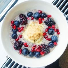 W E T | Breakfast on this cold rainy morning was a warm bowl of plain gluten free porridge (oats and water) with a coconut  cinnamon chia pudding blackberries blueberries pomegranate seeds  cashew peanut and hazelnut butter. So good…