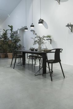 Black wooden table and metal chairs near white wall with three pendant lamps above table – Furniture – Commercial Office Furniture Inspiration Plus