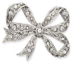 AN EXQUISITE DIAMOND BOW BROOCH The undulating foliate motif ribbon, of openwork design, set with single and old European-cut diamonds, mounted in platinum and 14K yellow gold, circa 1910