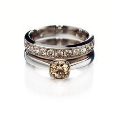 Päällä on valkokultainen rivisormus ruskeilla briljanttihiontaisilla timanteilla. Kivien yhteispaino on 0.77 ka. Istutusta koristaa siro krysantti. Sormuksen hinta on 3.090 euroa. Alla on myös valkokultainen sormus, nyt yhdellä isommalla ruskealla briljantilla. Kivi on painoltaan 0.50 ka ja sormuksen hinta on 3.480 euroa. Kultaseppä Kulmala.