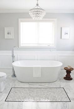 salle de bains blanche avec sol en marbre, baignoire et tabouret en bois
