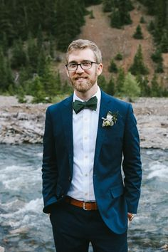 groom in blue suit and forest green bow tie