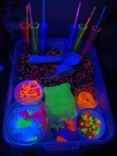 Glow In The Dark Sensory Box  (Aquarium Rock, Plastic Jewellery from Dollar Tree, Pony Beads, Felt, Feathers, Glow Sticks, anything neon really!)