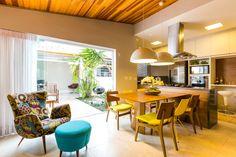 Aqui é possível ver toda a integração: jantar, cozinha, estar, churrasqueira e home office ao fundo.