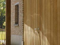 Voor de ramen gebruikten we Merantie Nemesu, een Afrikaanse houtsoort met een uitzonderlijke hardheid en structuur. Hierdoor is de houtsoort uitermate geschikt voor lakwerk. Het eiken luik werd volgens een zeer oud principe aan een smeedijzeren rail gehangen. Dit luik werd bovenaan afgewerkt met een loden slab. (Realisatie: Eddy De Prins - houten buiten- en binnenschrijnwerk)