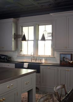 color palette - dark stone countertops, lighter subway backsplash, warm gray cabinets, dark wood island.