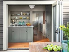 A folding patio door retracts to seamlessly connect this compact kitchen to an outdoor dining area.