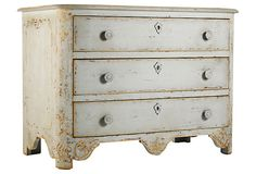 The simple shape, scalloped apron, and weathered, whitewashed finish of this three-drawer chest call to mind the Gustavian decor of a Swedish country home.