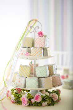 #γαμος στολισμος δυόροφη πιατελα με cakes και γιρλάντα λουλουδιων στη βαση, gamos stolismos diorofi piatela me cakes kai girlanda louloudiwn sti basi