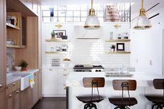 Elegant kitchen with brass kitchen pulls, a subway-tile wall, and drafter stools