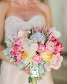Arrangements Floral & Party Design crafted a bouquet of coral charm peonies, king proteas, ranunculus, astilbe, and tulips. Wrapped in gold sequined trim, the finishing touch was a skeleton leaf.
