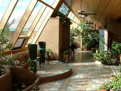 Earthship.  The concept of an 'earthship' was developed by American architect, Michael Reynolds. Most are single aspect with glazing to the south & a north rammed earth filled tyre retaining wall. He built two for actors Dennis Weaver & Keith Carradine.  The Weaver house in Ridgeway, Colorado came up for sale in 2004, hence many images.  They generally feature recycled materials & self-sufficiency in energy & water.