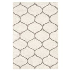 Showcasing a trellis-inspired motif and warm neutral hue, this artfully crafted shag rug is the perfect addition to your living room or den.