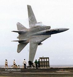 """Original Top Gun Dale """"Snort"""" Snodgrass flew for the movie, and has flown >4800 hours in the F14 Tomcat.  This photo: """"Lets Buzz the Tower"""", was snapped during a 1988 airshow as he whipped his jet past the USS America."""