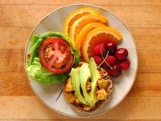 Vegan Breakfast Sandwich on a sprouted grain English muffin with scrambled tofu, melted Daiya cheddar, sliced avocado, hummus, butter lettuce, and tomato. Sliced orange, raspberries, and cherries.