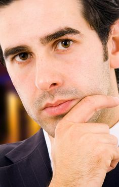 Close up portrait of a young business man with the office buildi