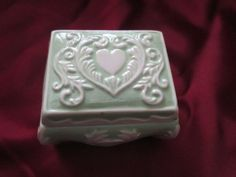 This sweet little green and white ceramic trinket box is great for display or to store little items in. It was made in 1974 by initials ER as marked on the bottom. Size is 2 1/2 x 2. The design is lovely and the heart on top makes it look antique as does the shape. Someone took a little love in making this beauty. It is adorable. There are a couple of small chips on the top that are only noticeable if closely inspected and shown in pictures.